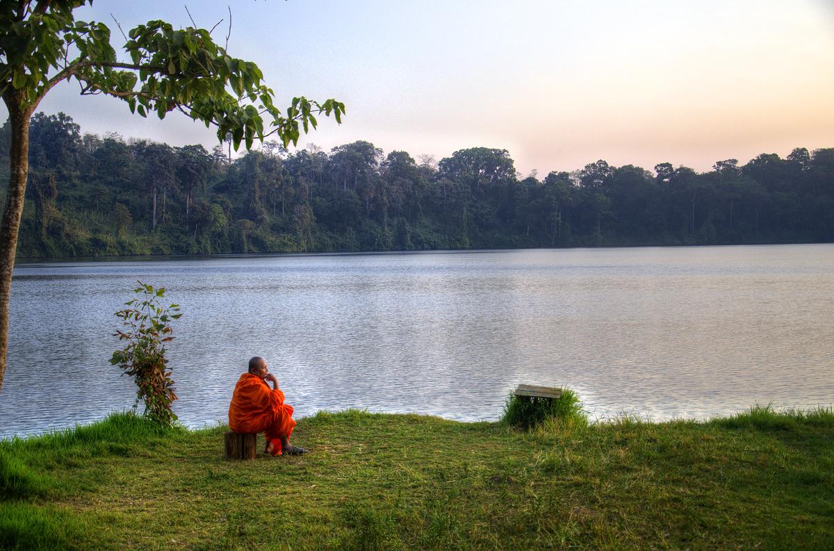 A buddhist monk, meditating and basking in the serenity at Yeak Loum Lake in Ratanakiri Province, Cambodia.