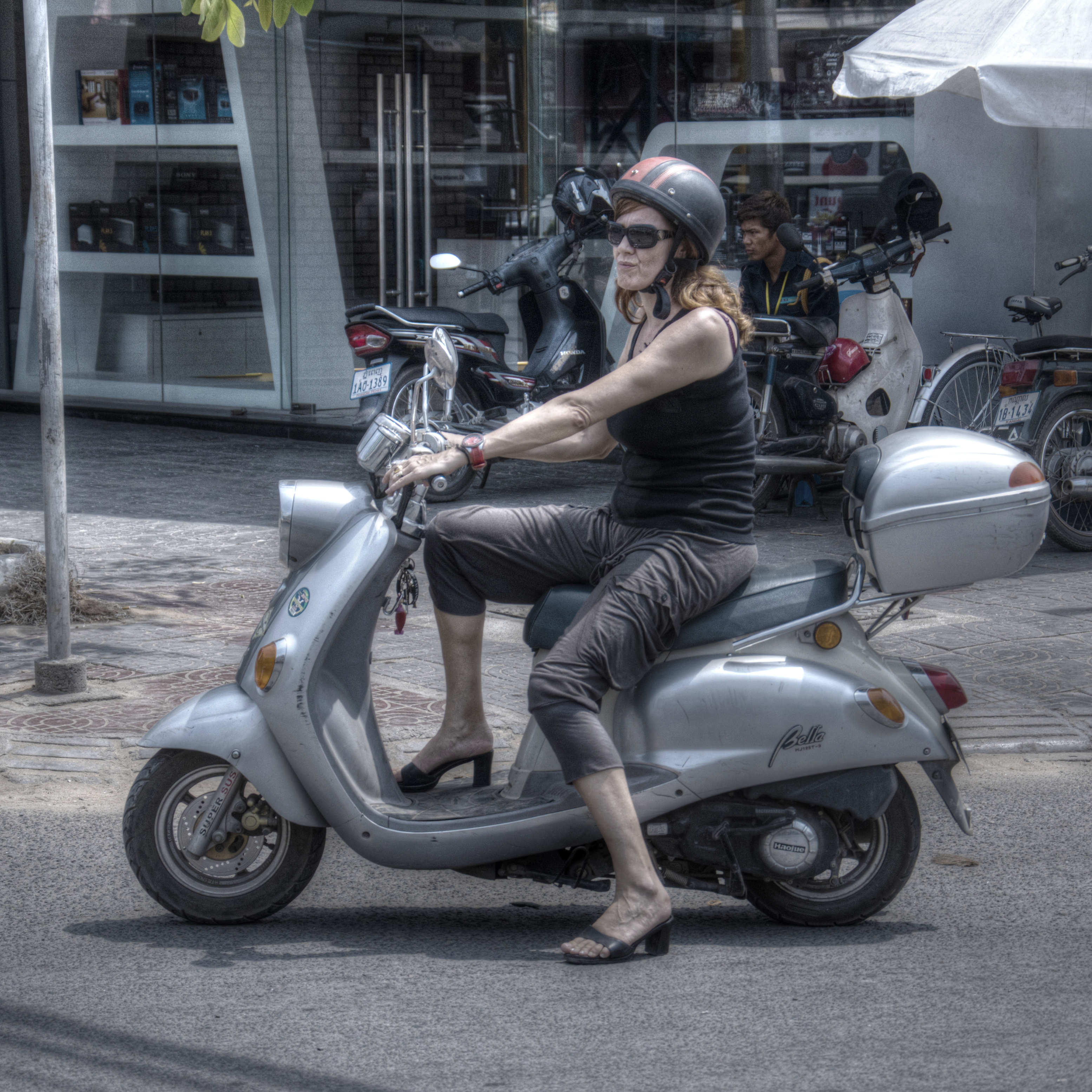 An expat in Phnom Penh, Cambodia, riding a German Zundapp Bella scooter.