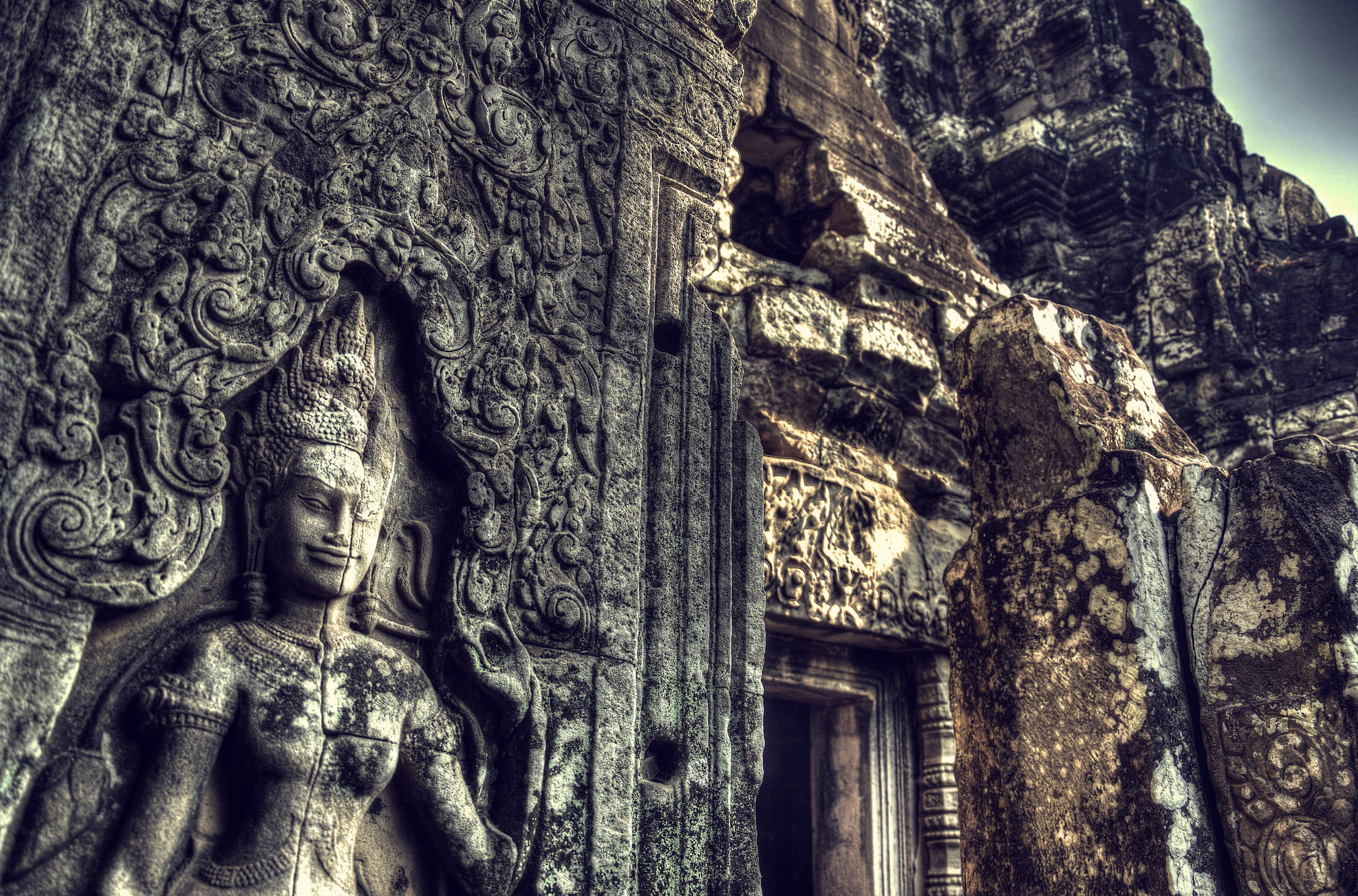 A carved sandstone female dancer gazes down through the millennia at Bayon Temple, Angkor Thom, Siem Reap City, Cambodia
