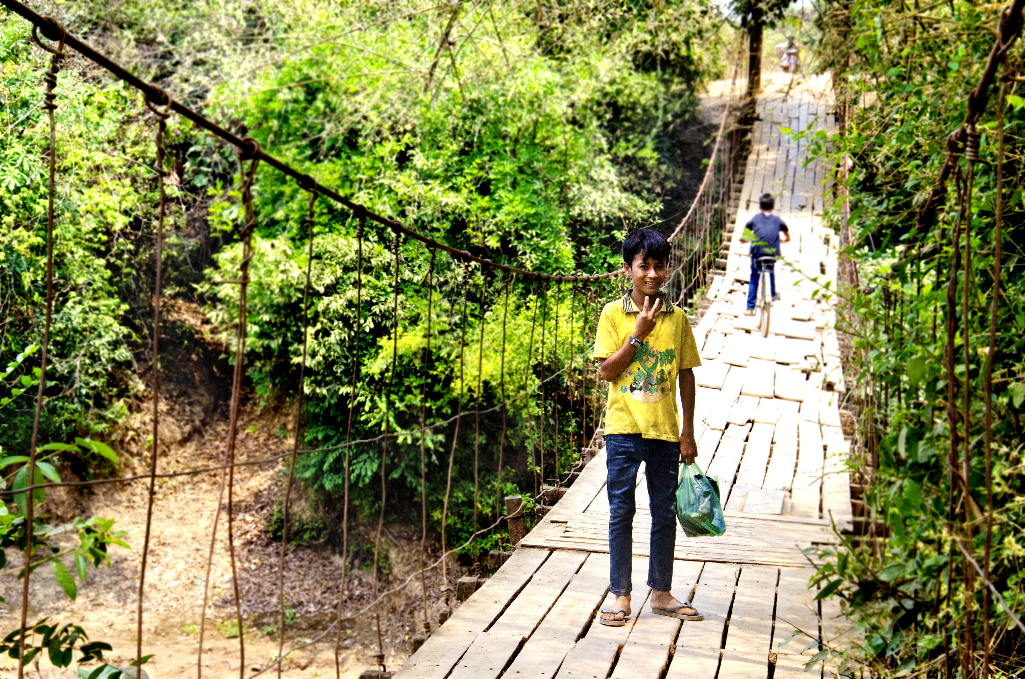 Kreung boy on swinging rope bridge