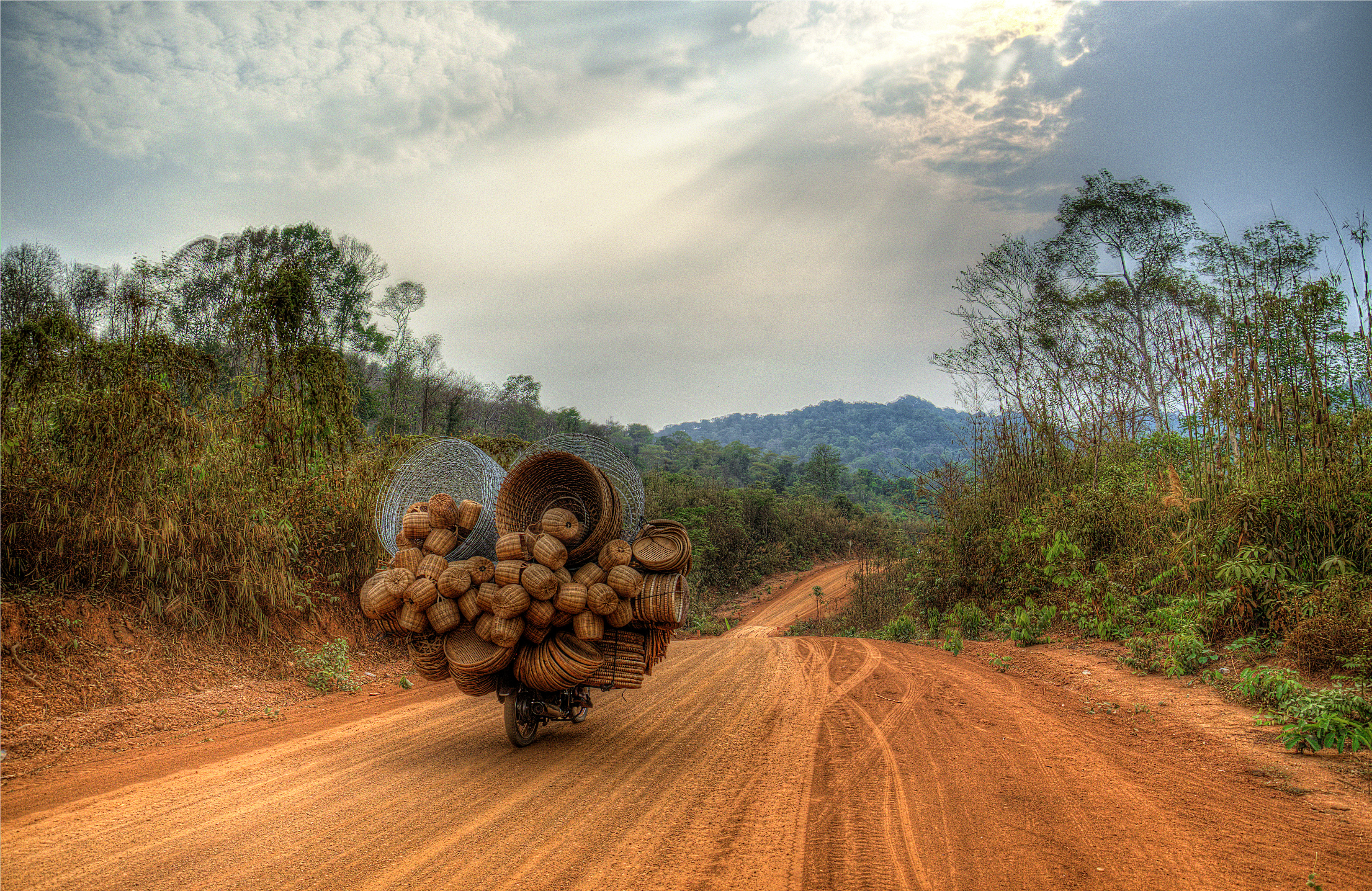 a cambodian itinerant seller of baskets, on a motorcycle