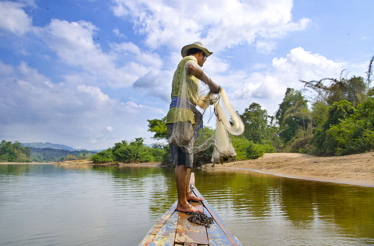 An indigenous Brao highlander  throwing a net.